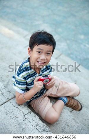 Happy asian boy with camera at park. Child relaxing outdoors in the day time, travel on vacation. Positive human emotion. - stock photo