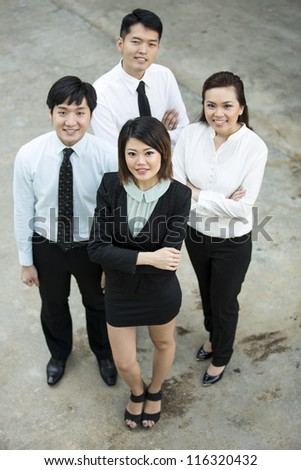Happy Asian Business colleagues looking up and smiling. - stock photo