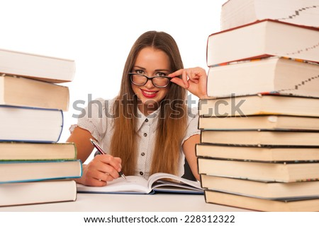 Happy asian caucasian girl lerning in study woth lots of books on the table isolated - stock photo