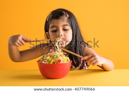 Happy Asian child eating delicious noodle, small indian girl eating noodles in red bowl with chopsticks, over yellow background - stock photo