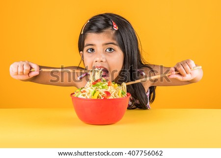 Happy Asian child eating delicious noodle, small indian girl eating noodles with chopsticks in red bowl, over colourful background