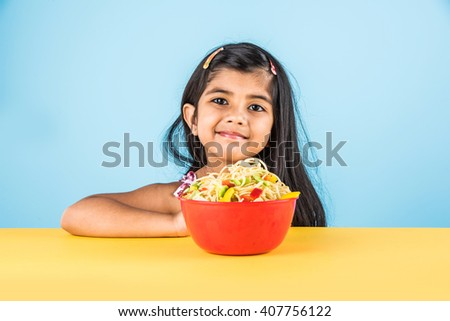 Happy Asian child eating delicious noodle, small indian girl eating noodles with chopsticks in red bowl, over colourful background - stock photo