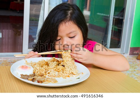 Happy Asian child eating delicious noodle, small Thai girl eating noodles in white bowl,Thai Asian child enjoy to eating delicious noodle
