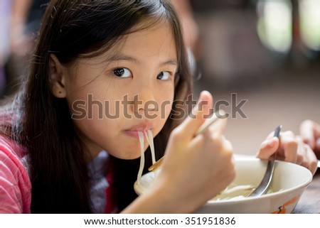 Happy Asian child eating delicious noodle with chopstick - stock photo