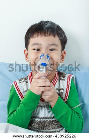 Happy asian child holds a mask vapor inhaler for treatment of asthma on sickbed in hospital. Breathing through a steam nebulizer. Concept of inhalation therapy apparatus. - stock photo