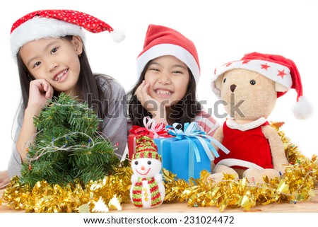Happy Asian child in Santa hat with Christmas decorations - stock photo