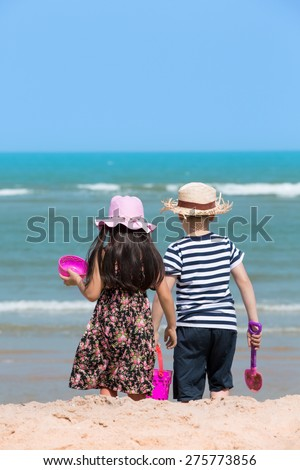 Happy asian child playing on tropical beach - stock photo