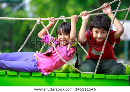 Happy asian child playing together on playground - stock photo