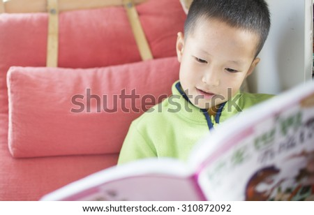 Happy  asian child reading book at home