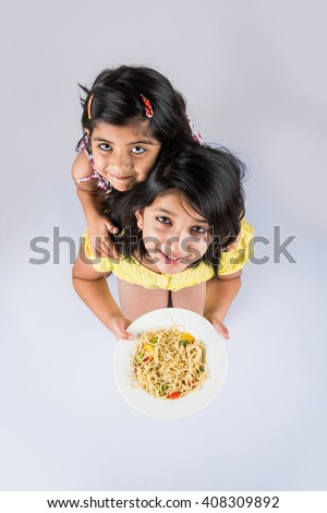 Happy Asian children eating delicious noodle, two cheerful little indian girls eating noodles in white dish isolated over white background, top view - stock photo