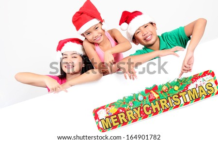 Happy asian children pointing to a christmas sign. - stock photo