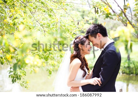 happy asian couple in wedding dress in a green park - stock photo