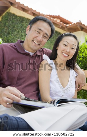 Happy asian couple reading novel outdoors