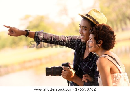 Happy asian couple tourists in nature - stock photo