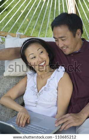 Happy asian couple using laptop while lying on hammock