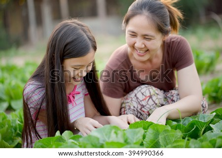 Happy Asian daughter gardening with her mother - stock photo