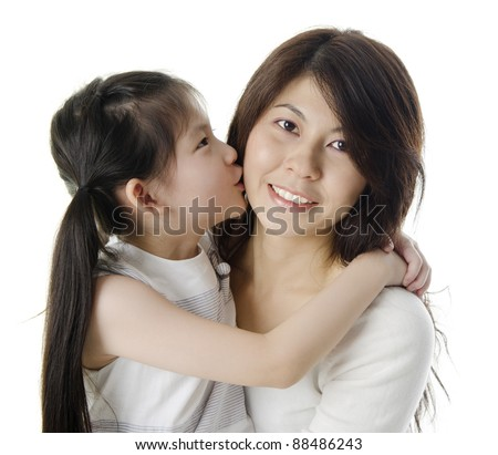 Happy Asian daughter kissing her mother on white background - stock photo