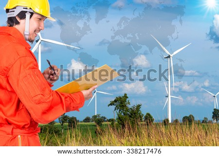 Happy Asian engineers writing the note pad on Wind turbine power generator with world map, industrial concept, Elements of this image furnished by NASA - stock photo