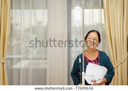 happy asian ethnic old woman patient in hospital ward with laboratory examination result on hand - stock photo