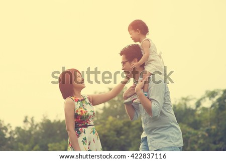 Happy Asian Family enjoying family time together in the park vintage tone - stock photo