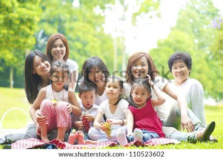 Happy Asian family enjoying picnic at outdoor park - stock photo