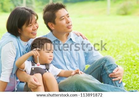 Happy Asian family having fun at outdoor park - stock photo