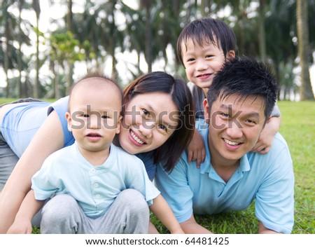 happy asian family having outdoor fun - stock photo