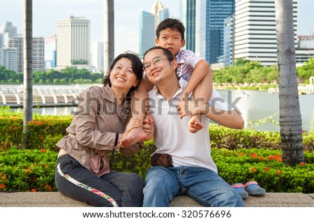 Happy Asian family in city garden. Man, woman and boy are Thai in Bangkok, Thailand, Southeast Asia.