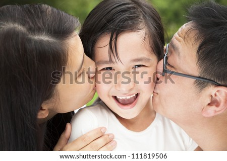happy Asian family in kissing - stock photo