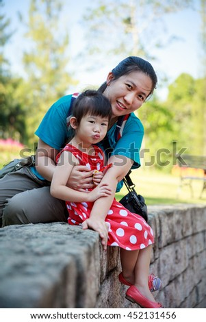Happy asian family, mother and lovely daughter smiling and looking at camera. Playful child and parent relaxing outdoors in the day time at park, travel on vacation. Positive human emotion.