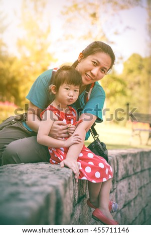 Happy asian family, mother and lovely daughter smiling and looking at camera. Playful child and parent relaxing outdoors in the day time at park with bright sunlight, travel on vacation.