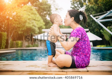 Happy asian family of mother and baby playing in the pool - stock photo