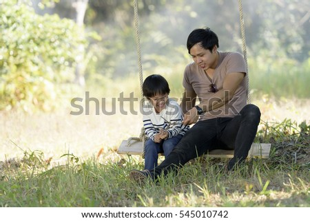 Happy asian family on a swing at field in the countryside. Smile with family on Thailand 2017