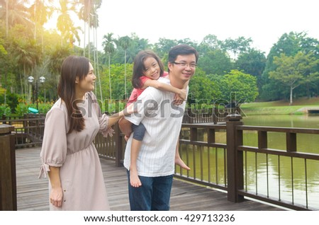 Happy Asian family outdoor. Father piggybacking his daughter walking in garden park with wife. Healthy lifestyle. - stock photo