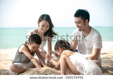 Happy Asian Family Playing on the beach - stock photo
