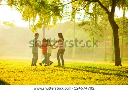 Happy asian family playing on the field during sunrise. People running in circle under the tree at outdoor green park.