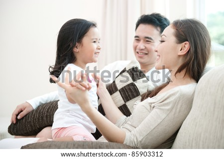 Happy Asian Family Playing with daughter in the living room - stock photo