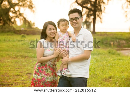 Happy Asian family portrait. Outdoor playing time during summer sunset. - stock photo