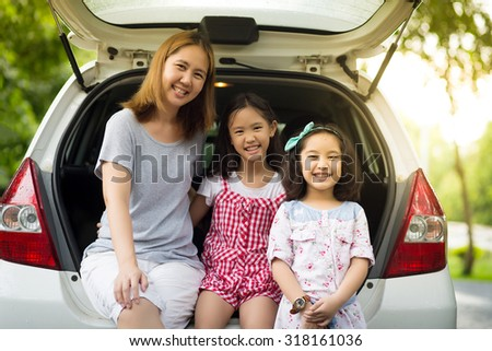 Happy Asian family sitting in the car - stock photo