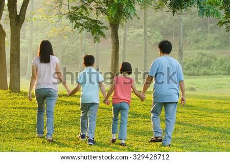 Happy Asian family walking - stock photo