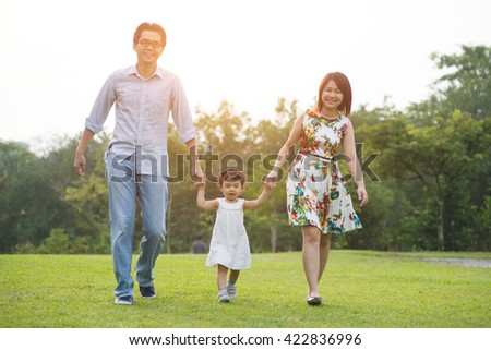 happy asian family walking on the park - stock photo