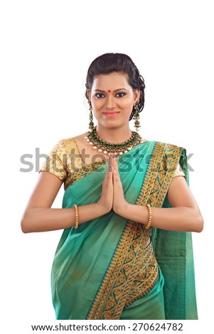 Happy Asian female in ethnic Sari welcoming on isolated white background. Traditional Indian Woman greeting with a smile.