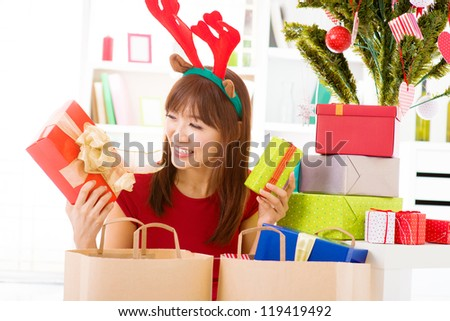 Happy Asian girl bought many Christmas present, preparation for Christmas, indoor. - stock photo