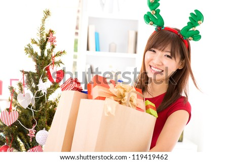 Happy Asian girl buying many Christmas gift, preparation for Christmas, indoor. - stock photo