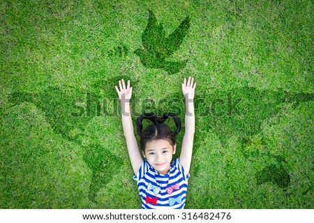Happy Asian girl child raising hands with happiness lying on grass peacefully with dove birds signs/ symbol and world map on green grass: Peaceful mind of a kid in beautiful and clean environment      - stock photo