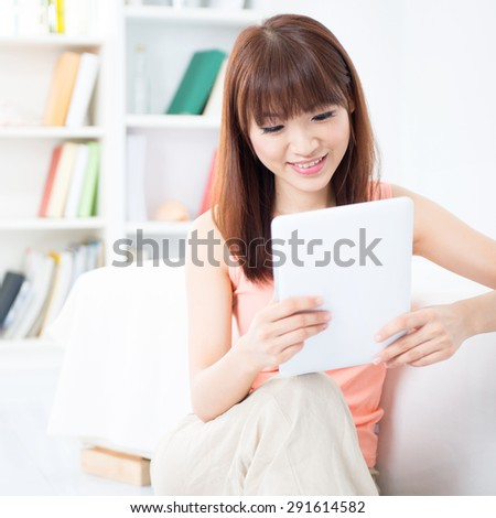 Happy Asian girl downloading new mobile apps, using tablet computer, social networks concept. Young woman indoors living lifestyle at home. - stock photo