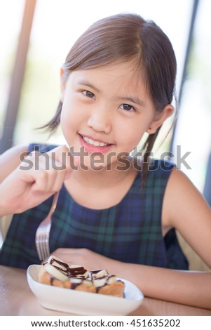 Happy Asian girl enjoy eating Banana split ice-cream with Honey toast. - stock photo