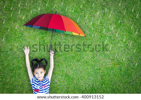 Happy asian girl kid raising hand lying on natural green grass lawn eco bio background holding colorful rainbow umbrella protect in rainy weather day: Insurance protection safety health care CSR ESG - stock photo