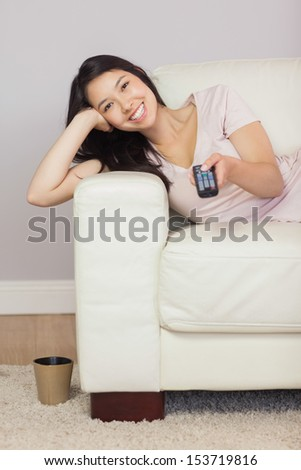 Happy asian girl lying on the sofa watching tv at home in the sitting room - stock photo