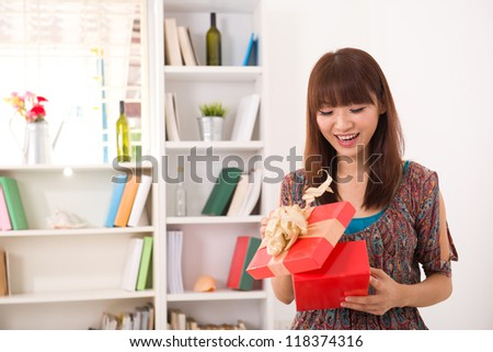 happy asian girl opening her present